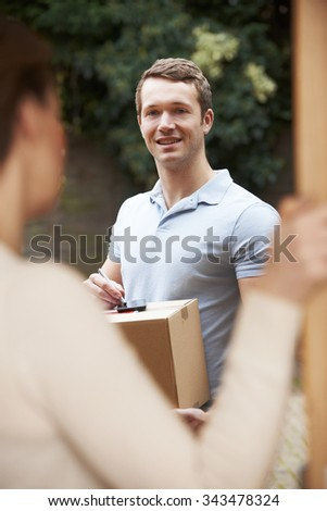 Courier Delivering Package To Domestic House - stock photo