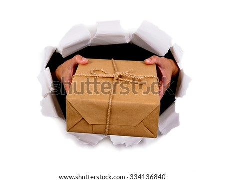 Courier hands delivering or giving parcel through torn white paper background - stock photo