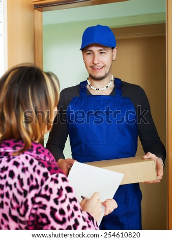 Courier in uniform brought package to girl at home - stock photo