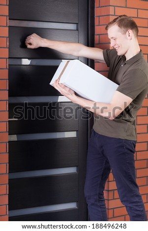 Courier knocking on doors and holding order - stock photo
