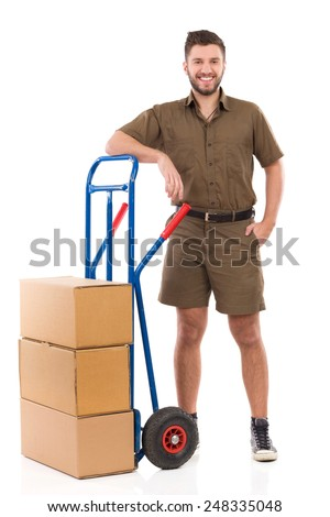 Courier posing with a push cart. Happy delivery man or mover standing relaxed close to push cart. Full length studio shot isolated on white. - stock photo
