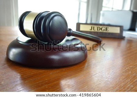 Court gavel on a desk with Judge nameplate in background                                - stock photo