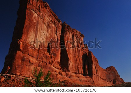 Courthouse Towers looms over Arches National Park in the early morning sun.