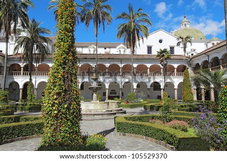 Courtyard gardens, fountain and dome of the church and monastery of San Francisco in Quito, Ecuador - stock photo