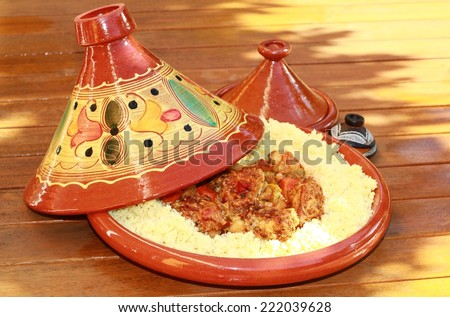 Couscous and meatballs presented in a beautiful tagine clay. - stock photo