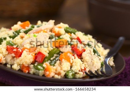 Couscous dish with chicken, green bean, carrot and red bell pepper served on plate with fork on the side (Selective Focus, Focus one third into the dish)  - stock photo