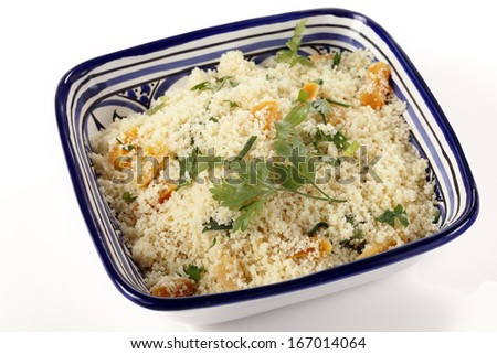 couscous mixed with chopped dried apricots and fresh parsley in a blue and white hand-made tunisian  bowl - stock photo