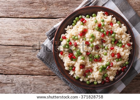 Couscous salad with green peas and pomegranate on the table. horizontal top view - stock photo