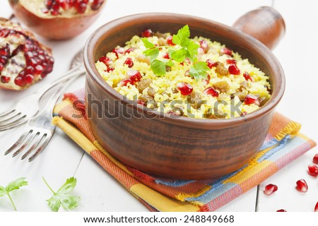 Couscous with pomegranate, raisins and spices on the table