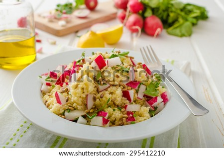 Couscous with radishes and herbs, topped herbs and olive oil, simple but delicious vegetarian food - stock photo