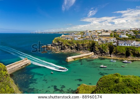 Cove and harbour of Port Isaac with arriving ship, Cornwall, England - stock photo