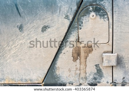 cover of an automobile gasoline tank with the lock on a fragment of the old dirty car for an abstract industrial background