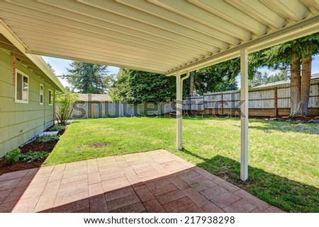 Covered backyard patio with brick tile floor. - stock photo