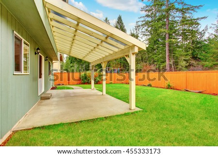 Covered backyard patio with concrete floor. Fenced brown backyard and well kept green lawn around