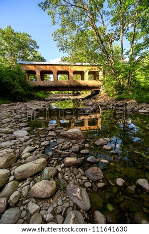 Covered bridge with reflection in vermont stream - stock photo