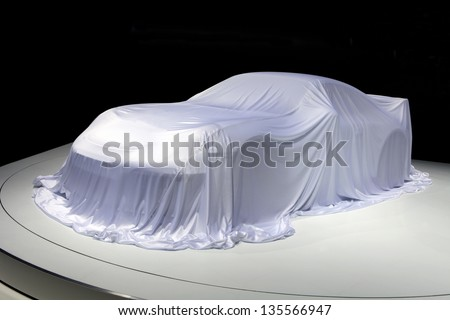 Covered car. Sport car covered with a white cloth in a exhibition on black background