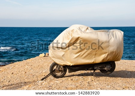 covered motorbike parked on the beach - stock photo