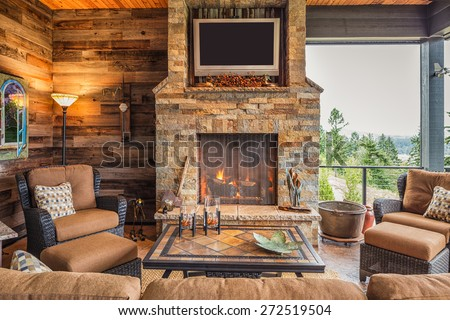 Covered Outdoor Patio Outside New Home with Couch, Chairs, TV, Fireplace, and Roaring Fire - stock photo