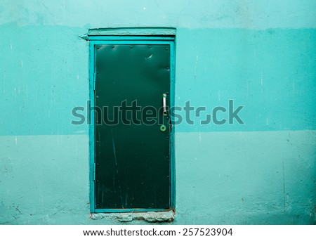 Covered with leather door with white metal handle and plastered wall around. - stock photo