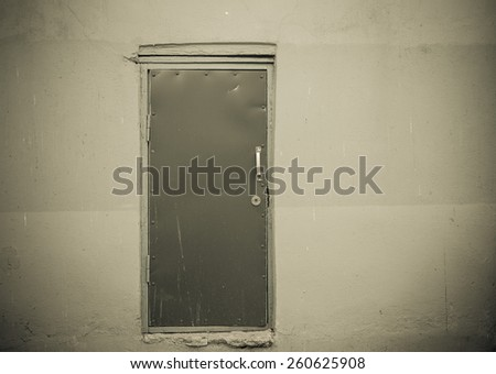 Covered with leather door with white metal handle and plastered wall around. Toned gray. - stock photo
