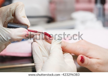 Covering nail varnish color close-up in a beauty salon. Manicure process.