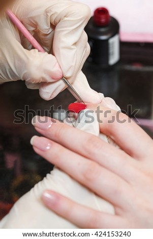 Covering nail varnish color close-up in a beauty salon. Manicure process. - stock photo