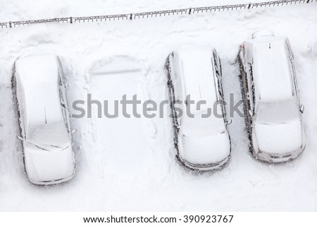 Covering with snow line of standing car with free parking place, winter and snowfall