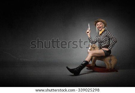 cow boy riding horse with unbelieving expression, dark background - stock photo