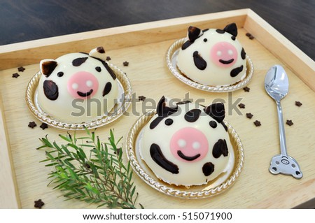 cow cakes decorated and chocolate stars on wood background