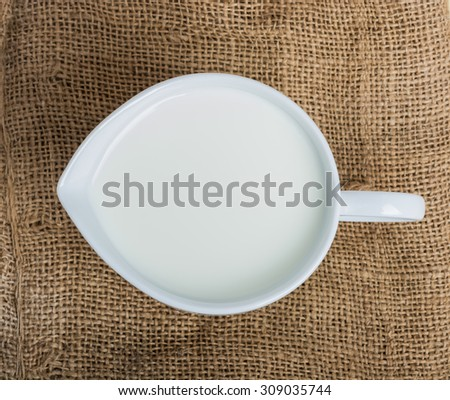 Cow milk and ceramic jug on wooden table - stock photo
