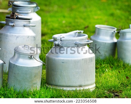 cow's milk in various metallic cans - stock photo