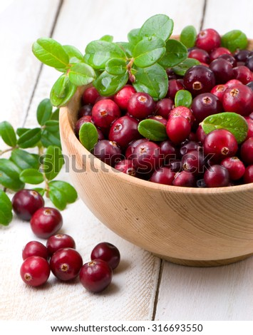 Cowberry with green leaflets in wooden cup - stock photo