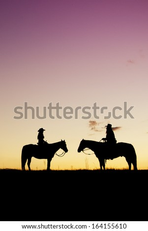 Cowboy and cowgirl silhouette at colorful sunset - stock photo