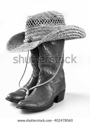 Cowboy boots and straw hat in black and white. - stock photo