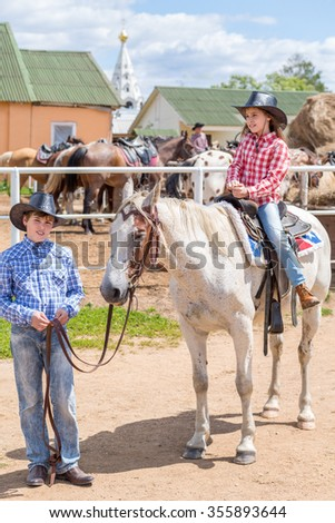 cowboy brother holds the horse of his sister by the reins - stock photo