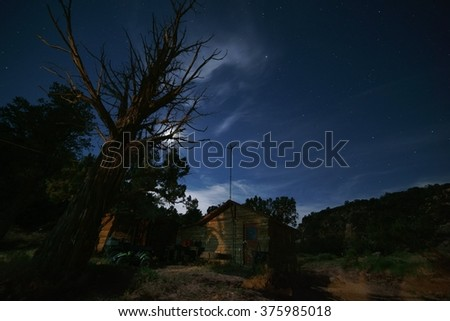 Cowboy bunkhouse and night sky with large juniper tree in foreground.    The blue night sky has a few clouds and stars while a sandstone canyon rim is in the background.                       - stock photo