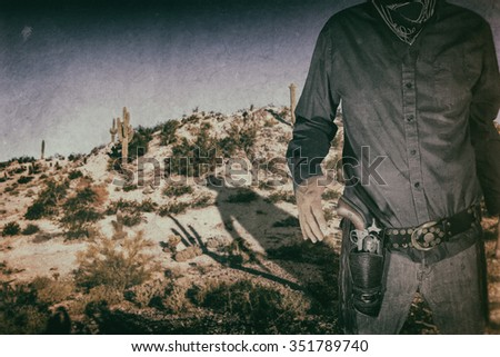 Cowboy Cactus Desert Shadow. Cowboy standing in a cactus desert, ready to draw his Colt 45 revolver. His shadow cast over the desert. Edited with a vintage film effect.