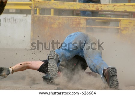 Cowboy falling off bull - stock photo