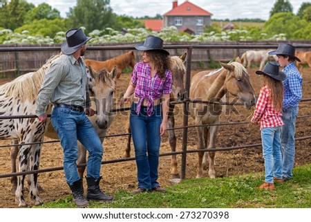 cowboy family of four feeding foals hay - stock photo