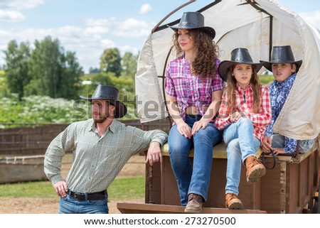 cowboy family of four in a wagon - stock photo