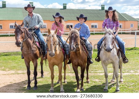 cowboy family of four on horses on background of paddock - stock photo