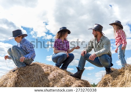 cowboy family of four sitting on haystacks - stock photo