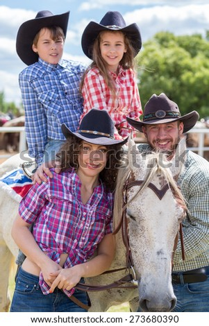 cowboy family of four with a horse closeup - stock photo