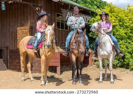 cowboy family of three on horses - stock photo