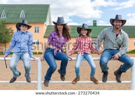 cowboy family sit on the fence of the corral - stock photo