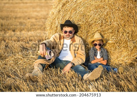 Cowboy father and a son enjoy country life sitting against hay stack on a sunny evening day after hard day