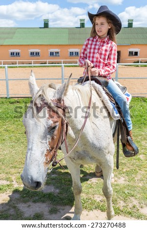cowboy girl on horseback looks into the distance - stock photo