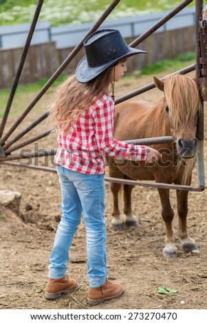 cowboy girl with a pony foal - stock photo