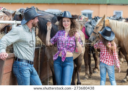 cowboy girl with her perents feed the horses hay - stock photo