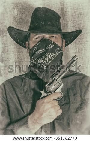 Cowboy Gunslinger Poses for Portrait. Gun-slinging cowboy bandit poses for a portrait. Edited with a vintage film effect. - stock photo